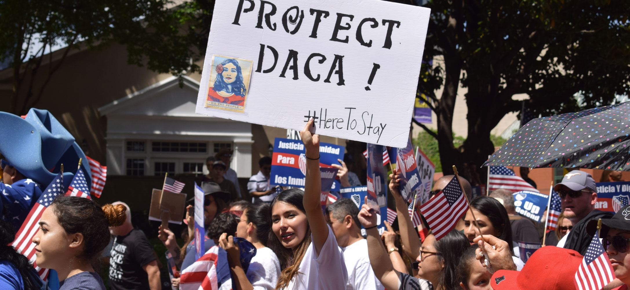 People holding a sign to protect DACA